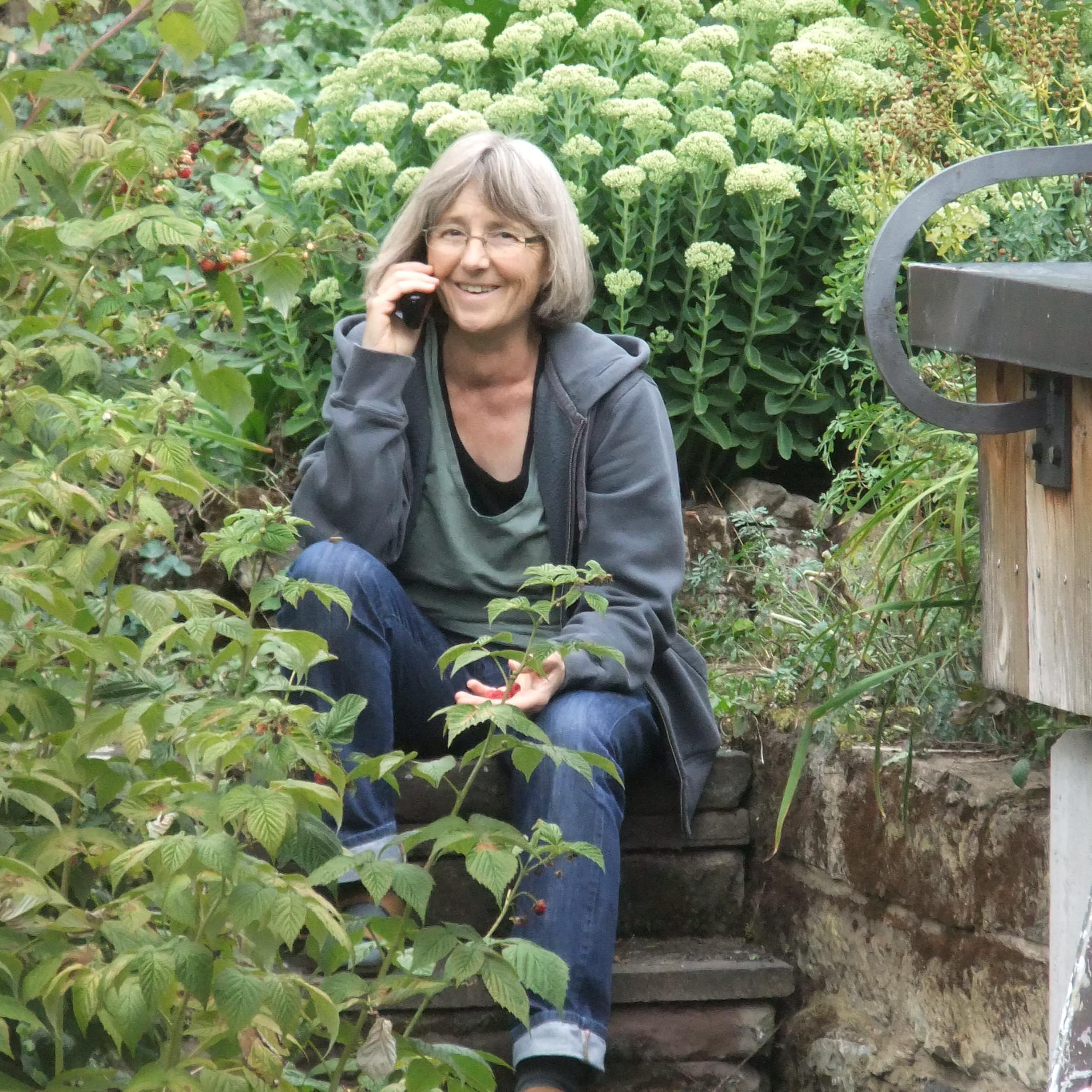 Stefanie Seemann sitzt in ihrem Garten und telefoniert