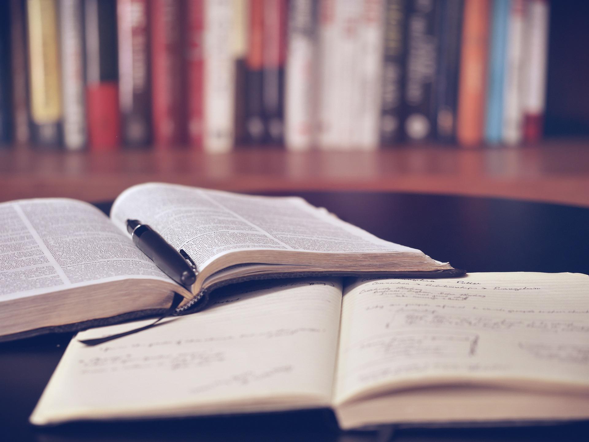 Symbolbild: Geöffnete Bücher mit Stift im Büro