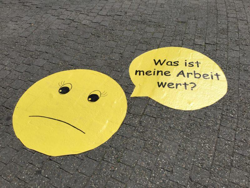 """Trauriger Emoji mit Sprechblase: """"Was ist meine Arbeit wert?"""""""